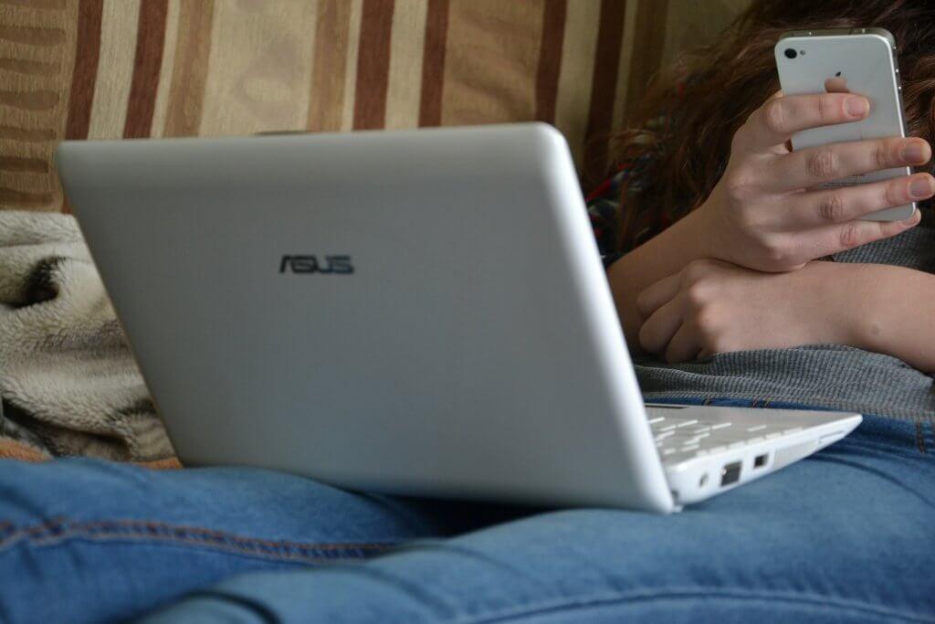 une fille qui est et sur son téléphone et sur son ordinateur en train de les manipuler